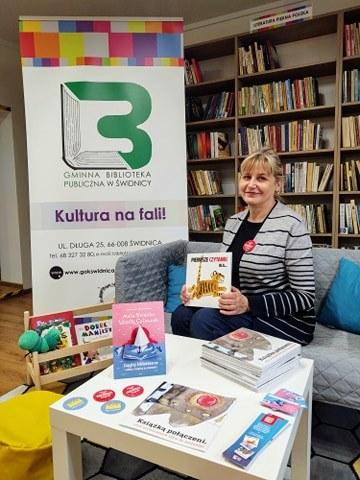 Pani Bożena Trubiłowicz kierownik biblioteki siedzi na kanapie i trzeymająć książkę promuje wyprawkę czytelniczą dla przedszkolaka