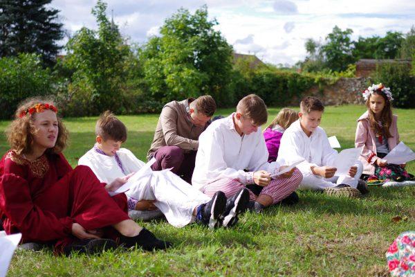 Dzieci czytają tekst na polanie