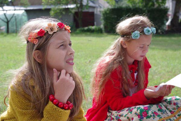 dwie dziewczynki czytają tekst na polanie