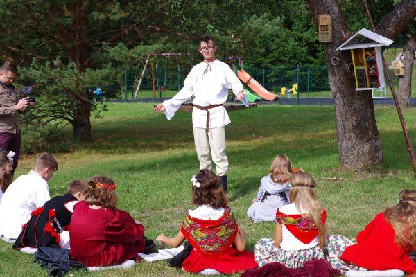 Dzieci uczestniczą w zajęciach na polanie przed szkołą