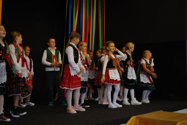 Dzieci w strojach ludowych tańczą na scenie
