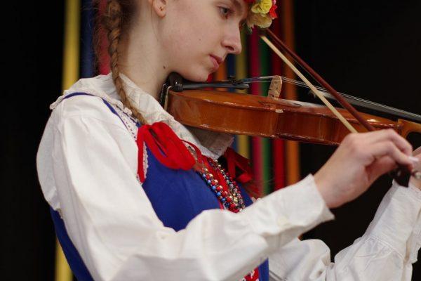 Dziewczyna w stroju ludowym gra na skrzypcach