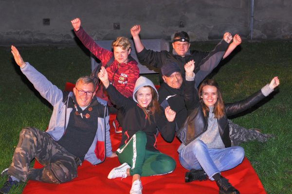 zdjęcie przestawia siedzących pracowników na czerwonym dywanie