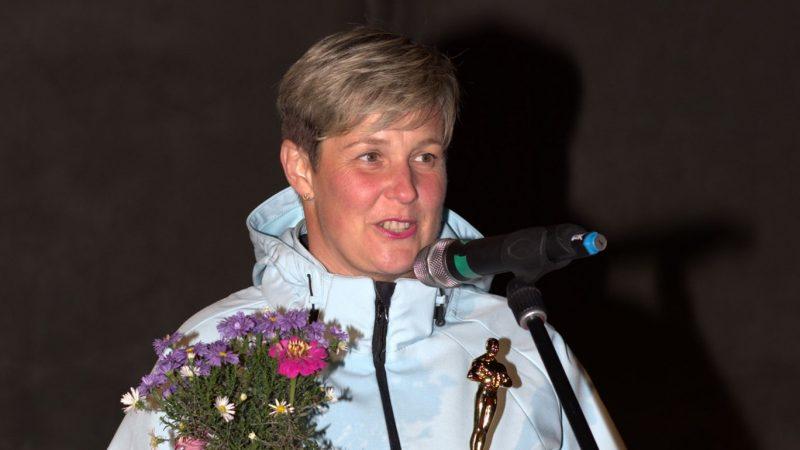 Kobieta przemawia tzrymajać kwiaty i statuetkę